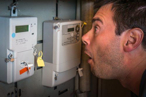 man kijkt met opend mond naar elektriciteitsmeter