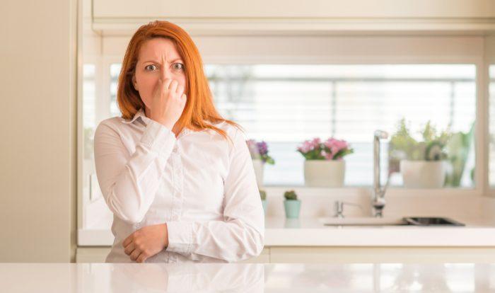 Vrouw met rost haar die haar neus toeknijpt