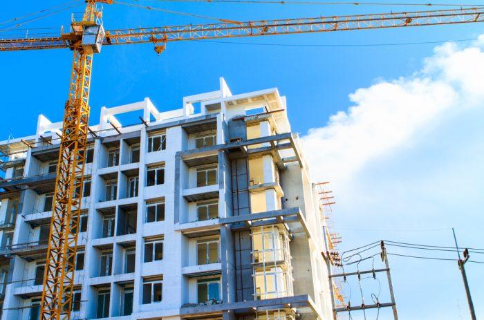 Constructie van appartementsgebouw met gele kraan