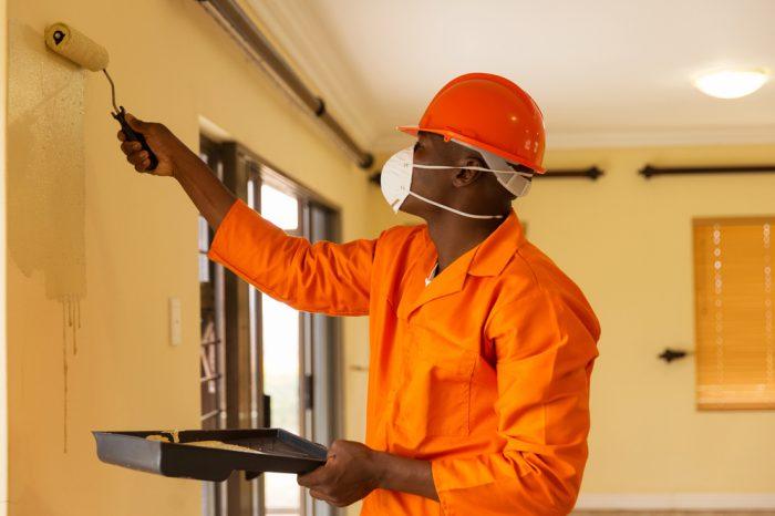 Man die binnen een muur schildert